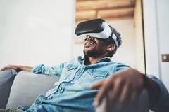 Conceito da tecnologia, do jogo, do entretenimento e dos povos Homem africano farpado que aprecia auriculares dos vidros da reali Foto de Stock