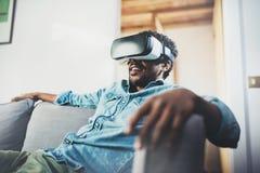 Conceito da tecnologia, do jogo, do entretenimento e dos povos Homem africano novo que aprecia auriculares dos vidros da realidad Fotografia de Stock Royalty Free