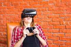 Conceito da tecnologia, do jogo, do entretenimento e dos povos - jovem mulher com os auriculares da realidade virtual, gamepad do Imagem de Stock