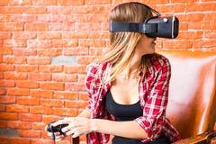 Conceito da tecnologia, do jogo, do entretenimento e dos povos - jovem mulher com os auriculares da realidade virtual, gamepad do fotografia de stock royalty free