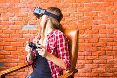 Conceito da tecnologia, do jogo, do entretenimento e dos povos - jovem mulher com os auriculares da realidade virtual, gamepad do Fotografia de Stock
