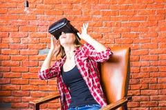 Conceito da tecnologia, do VR, do entretenimento e dos povos - jovem mulher feliz com os auriculares da realidade virtual ou os v imagens de stock royalty free