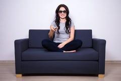 conceito da televisão 3d - jovem mulher que senta-se no sofá e na observação Imagens de Stock