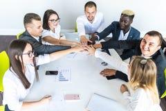 Conceito da unidade Close-up dos multi povos étnicos que mantêm as mãos unidas ao sentar-se em torno da mesa imagens de stock royalty free