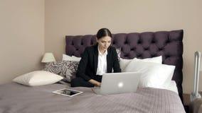 Conceito da viagem de negócios - mulher de negócio feliz com o computador que encontra-se no hotel na cama que trabalha na sala m vídeos de arquivo