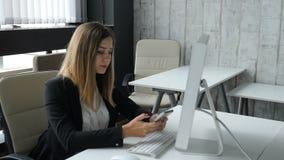 Conceito da vida do escritório A mulher de negócio atrativa nova senta-se pelo computador no escritório com um telefone em suas m vídeos de arquivo