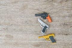 Conceito da violência - brinque armas no banco de madeira fotografia de stock