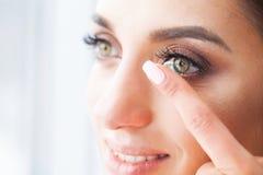 Conceito da visão Close-up disparado da lente de contato vestindo da jovem mulher imagens de stock