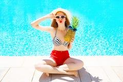 conceito das férias de verão - mulher com o abacaxi que tem o divertimento sobre uma associação de água azul fotografia de stock royalty free