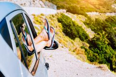 Conceito das férias do carro da viagem por estrada do verão Pés da mulher para fora a janela no carro na estrada de enrolamento d imagens de stock royalty free