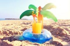 Conceito das férias e do verão com o flutuador da associação da forma fresco do suco de fruta e da palma sobre a areia na praia fotografia de stock royalty free