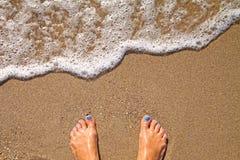Conceito das férias, pé das mulheres perto da espuma do mar na areia do ouro foto de stock