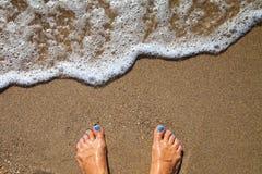 Conceito das férias, pé das mulheres perto da espuma do mar na areia do ouro imagens de stock royalty free