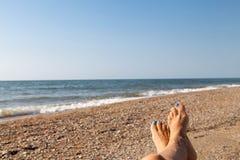 Conceito das férias, pedicure azul do pé bonito das mulheres perto do lan do mar imagens de stock royalty free