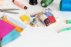 Conceito das ferramentas, dos retalhos, da costura e da forma da costura - close up na mesa branca do trabalho no estúdio, almofa Imagens de Stock