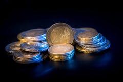 Conceito das moedas do Euro das pilhas isoladas no preto Fotografia de Stock