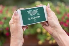 Conceito das notícias do mundo em um smartphone Fotos de Stock