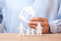 Conceito de alugar a casa, o crédito ou o seguro O homem na camisa está guardando a casa e a família está estando ao lado dele imagem de stock