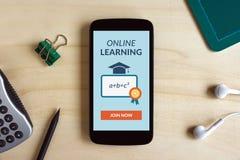 Conceito de aprendizagem em linha na tela esperta do telefone na mesa de madeira imagens de stock