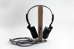 Conceito de Audiobook dos fones de ouvido e dos livros, fones de ouvido com livros imagens de stock royalty free