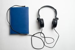 Conceito de Audiobook dos fones de ouvido e dos livros, fones de ouvido com livros foto de stock royalty free