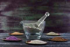 Conceito de Beaty e de termas: almofariz de vidro com argila verde no meio do copo do metal com argila vermelha, roxa, amarela, b Imagem de Stock