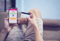Conceito de compra em linha - homem novo que usam a compra do smartphone no mercado do Web site em linha e mãos que guardam o car fotografia de stock