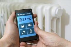 Conceito de controle home esperto O homem está ajustando a temperatura com smartphone fotos de stock royalty free