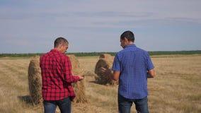 Conceito de cultivo esperto da agricultura dos trabalhos de equipe dois trabalhadores dos fazendeiros dos homens que andam estuda filme