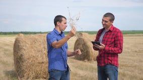 Conceito de cultivo esperto da agricultura dos trabalhos de equipe dois trabalhadores dos fazendeiros dos homens que estudam um m vídeos de arquivo