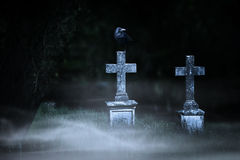 Conceito de Dia das Bruxas, cruzes de pedra na noite no cemitério nevoento Fotos de Stock Royalty Free