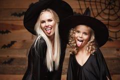 Conceito de Dia das Bruxas - mãe caucasiano bonita do close up e sua filha em trajes da bruxa que comemoram Dia das Bruxas que le Foto de Stock Royalty Free