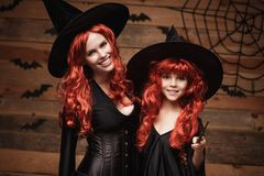 Conceito de Dia das Bruxas - mãe caucasiano bonita e sua filha com cabelo vermelho longo em trajes da bruxa e na varinha mágica q Fotografia de Stock