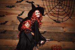 Conceito de Dia das Bruxas - mãe caucasiano bonita e sua filha com cabelo vermelho longo nos trajes da bruxa que voam com mágica foto de stock