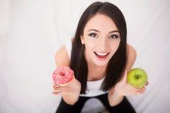 Conceito de dieta Jovem mulher que escolhe entre frutos e doces Fotografia de Stock