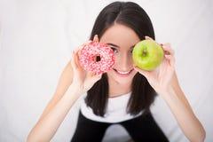 Conceito de dieta Jovem mulher que escolhe entre frutos e doces Imagem de Stock Royalty Free