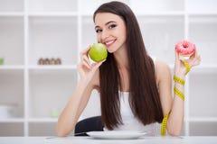 Conceito de dieta Jovem mulher que escolhe entre frutos e doces Fotos de Stock Royalty Free