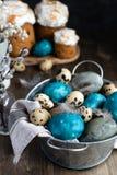 Conceito de easter da mola, - ovos da páscoa naturalmente tingidos, ovos de codorniz, penas, bolo de easter, fundo de madeira es foto de stock