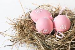 Conceito de Easter Ninho do feno com os ovos cor-de-rosa pintados no branco Fim acima Foto de Stock Royalty Free