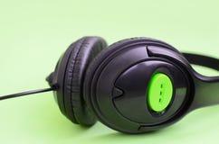 Conceito de escuta da música Mentiras pretas dos fones de ouvido no fundo verde imagem de stock royalty free
