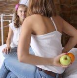 Conceito de família A mamã mantém-se atrás do fruto e oferece-se sua filha escolher Fotos de Stock Royalty Free