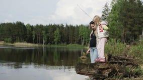 Conceito de família Mulher gravidanova de com a menina que descansa no lago vídeos de arquivo