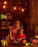 Conceito de família Família que planta flores em casa Mãe da ajuda da criança pequena a importar-se com plantas, família Trabalho fotografia de stock royalty free