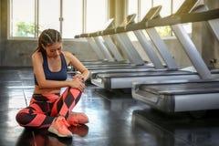 Conceito de ferimento dos esportes As mulheres s?o dor do joelho do exerc?cio errado menina do atleta que faz massagens os m?scul imagens de stock royalty free