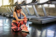 Conceito de ferimento dos esportes As mulheres s?o dor do joelho do exerc?cio errado menina do atleta que faz massagens os m?scul fotos de stock