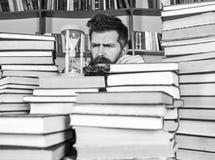 Conceito de fluxo do tempo O homem, cientista nos vidros olha a ampulheta Professor ou estudante com barba que estudam na bibliot foto de stock