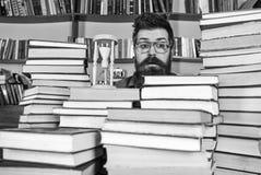 Conceito de fluxo do tempo Professor ou estudante com barba que estudam na biblioteca O homem, cientista nos vidros olha a ampulh fotografia de stock royalty free