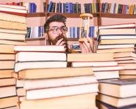 Conceito de fluxo do tempo Professor ou estudante com barba que estudam na biblioteca O homem, cientista nos vidros olha a ampulh imagens de stock