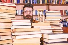 Conceito de fluxo do tempo Professor ou estudante com barba que estudam na biblioteca O homem, cientista nos vidros olha a ampulh fotos de stock royalty free