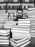 Conceito de fluxo do tempo Professor ou estudante com barba que estudam na biblioteca O homem no tempo de observação da cara séri foto de stock